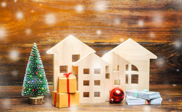 Houten huizen, kerstboom, geld en geschenken.