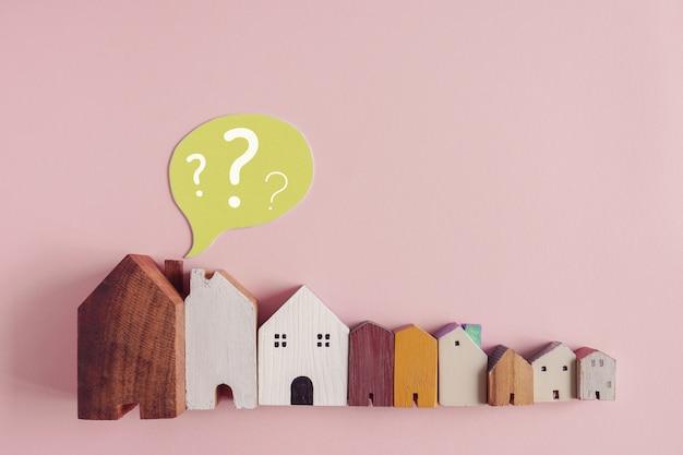 Houten huizen met vraagtekens