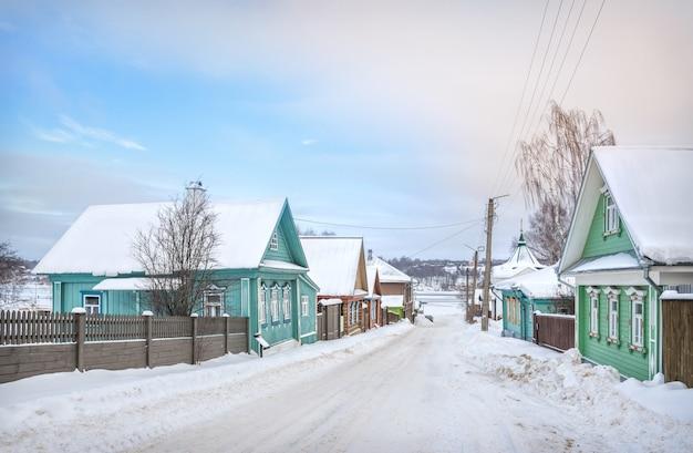 Houten huizen op nikolskaya street en een uitzicht op de bevroren wolga in plyos in het licht van een winterdag onder een blauwe hemel