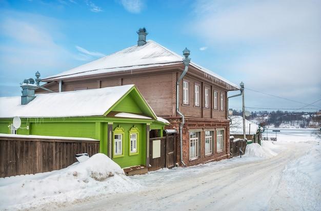 Houten huizen op nikolskaya street in plyos in het licht van een winterse dag onder een blauwe hemel