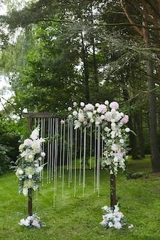 Houten huwelijksboog versierd met verse exotische bloemen buitenshuis