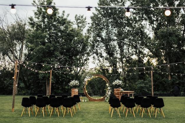 Houten huwelijksboog versierd met witte bloemen met groen staande in het midden van de huwelijksceremonie. zwarte stoelen aan zijkanten.