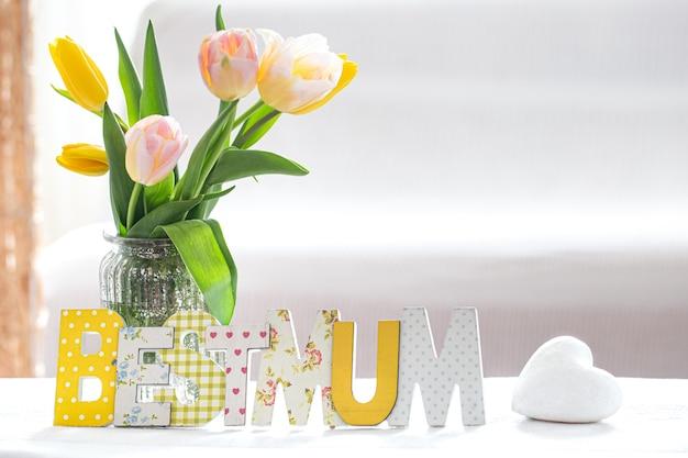 Houten inscriptie voor moederdag op een houten tafel in de woonkamer met een vers mooi boeket van lentetulpen.