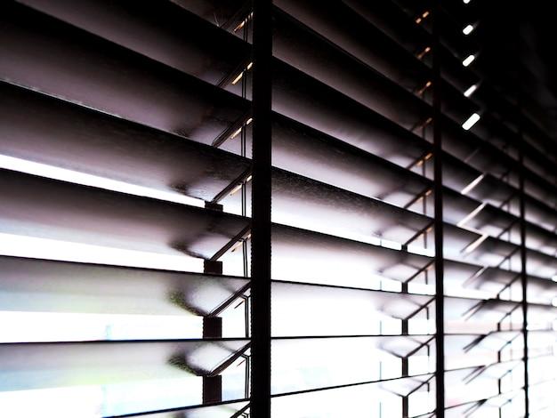 Houten jaloezieën, gordijnen sieren de kamer en beschermen het zonlicht
