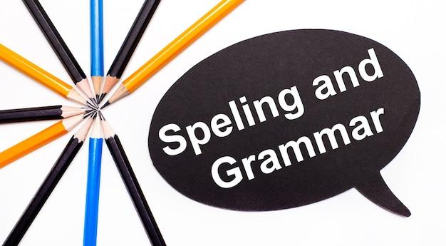 Houten kaart met de tekst spelling and grammar op een zwarte achtergrond in de buurt van veelkleurige potloden.