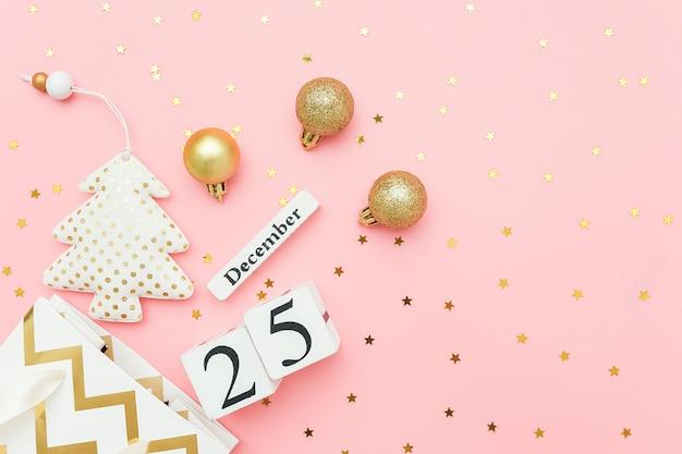 Houten kalender 25 december, textielkerstboom, gouden kerstballen, sterrenconfetti op roze. vrolijk kerstconcept.