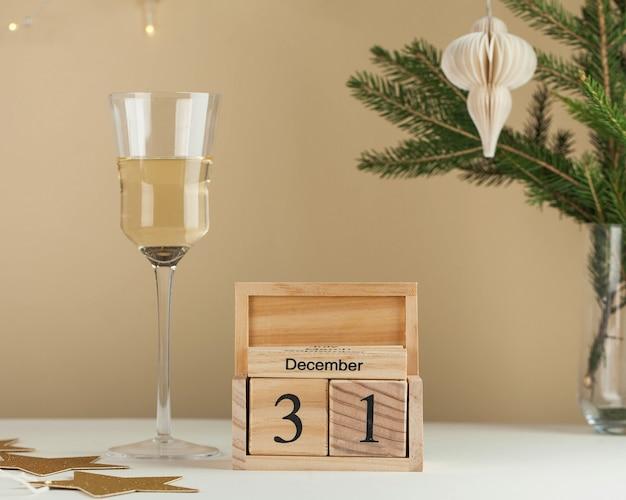 Houten kalender december nieuwjaarsachtergrond een glas wijn een boomtak een slinger minimalisme