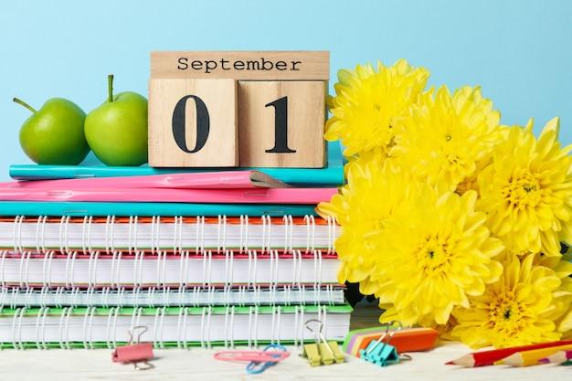 Houten kalender met 1 september en schoolspullen op blauw