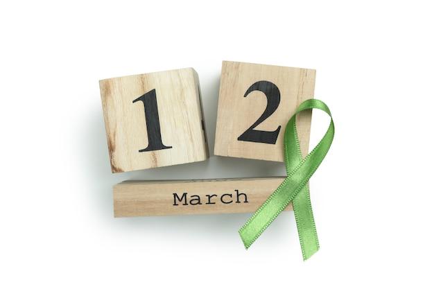 Houten kalender met 12 maart en groen voorlichtingslint dat op wit wordt geïsoleerd