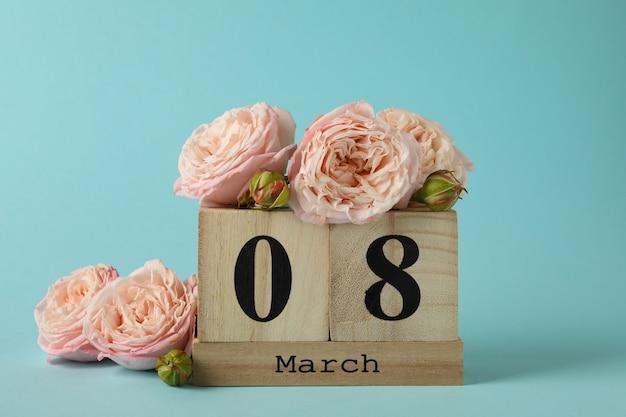 Houten kalender met 8 maart en rozen op blauwe achtergrond