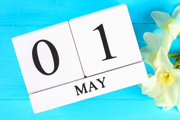Houten kalender met de tekst: 1 mei. witte bloemen van narcissen. dag van de arbeid en lente