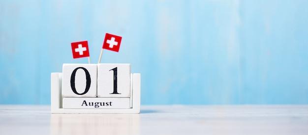 Houten kalender van 1 augustus met miniatuur vlaggen van zwitserland. zwitserse nationale feestdag en gelukkig feestconcepten