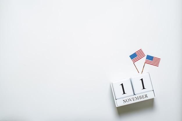 Houten kalender van 11 november met miniatuur amerikaanse vlaggen. concepten voor het vieren van wereldveteranendag
