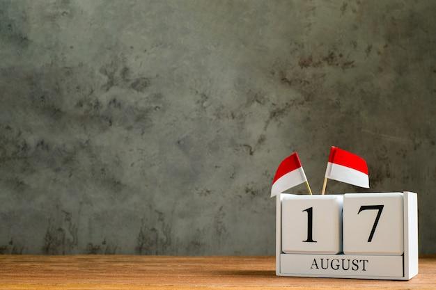 Houten kalender van 17 augustus met miniatuur indonesië vlaggen. de onafhankelijkheidsdag van indonesië, de dag van de natievakantie en gelukkige vieringsconcepten