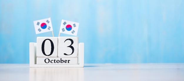 Houten kalender van 3 oktober met miniatuur vlaggen van de republiek korea.