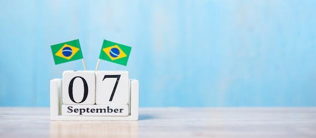 Houten kalender van 7 september met miniatuur vlaggen van brazilië.
