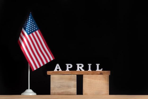 Houten kalender van april met usa vlag op zwarte ruimte