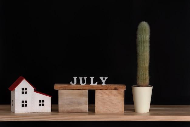 Houten kalender van juli, cactus en huismodel op zwarte achtergrond. kopieer ruimte.
