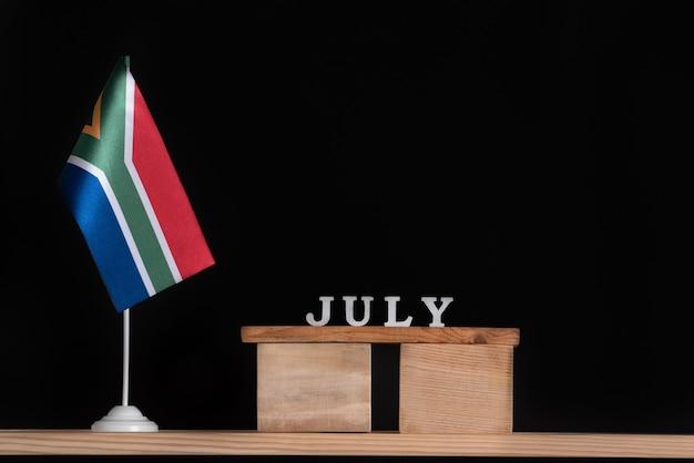 Houten kalender van juli met rsa vlag op zwarte achtergrond. data van zuid-afrika in juli.