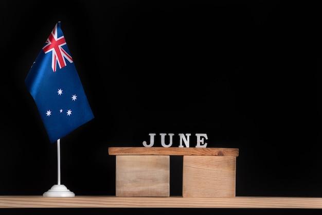 Houten kalender van juni met australische vlag op zwarte muur