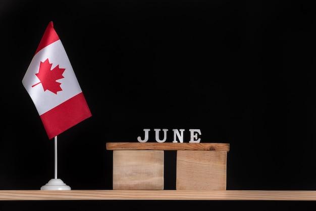 Houten kalender van juni met canadese vlag op zwart