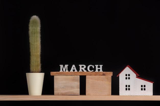 Houten kalender van maart, cactus en huismodel op zwarte achtergrond. kopieer ruimte.