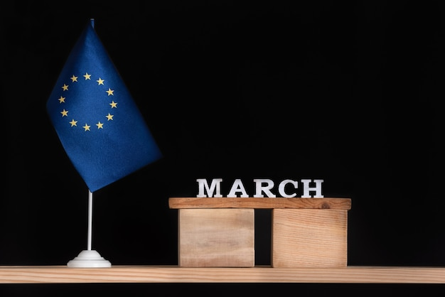 Houten kalender van maart met vlag eu op zwarte achtergrond. feestdagen van de europese unie in maart.