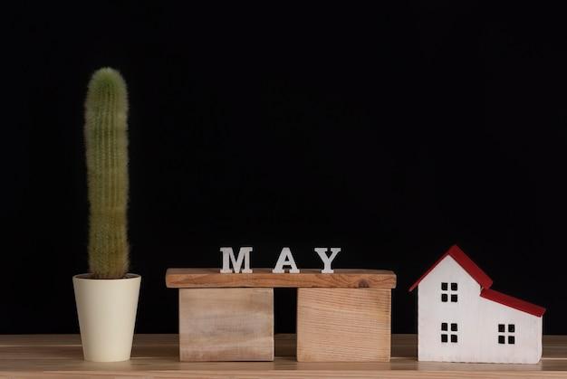 Houten kalender van mei, cactus en huismodel op zwarte achtergrond. kopieer ruimte.