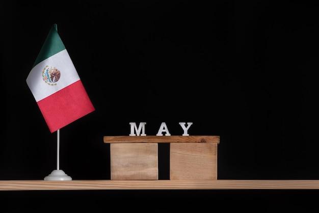Houten kalender van mei met vlag van mexico op zwart