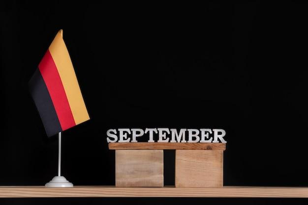 Houten kalender van september met duitse vlag op zwarte achtergrond. datums in duitsland in september.