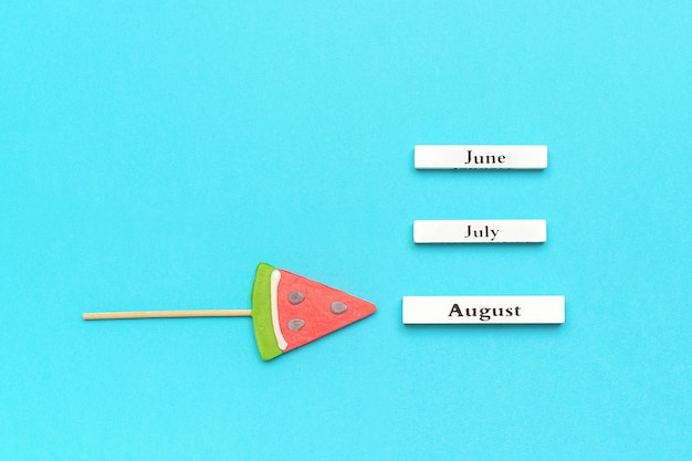 Houten kalender zomermaanden augustus, juni, juli en watermeloen lolly op stok op blauw