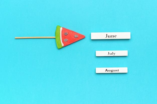 Houten kalender zomermaanden juni, juli, augustus en watermeloenlolly.