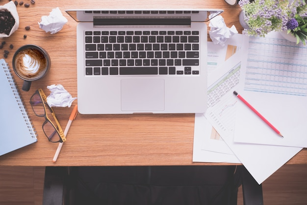 Houten kantoortafel met laptop en papierwerk, latte koffiekopje, verfrommeld papier.