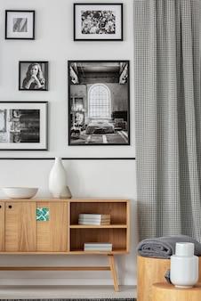 Houten kast tegen witte muur met galerij van posters in lichte woonkamer interieur. echte foto
