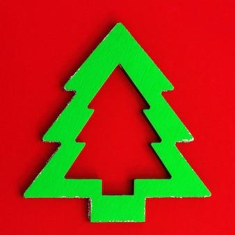 Houten kerstboom groene kleur met schaduw op rood papier met lege ruimte