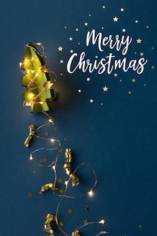 Houten kerstboom in de vorm van een raket op een donkerblauwe achtergrond. straal spoor van slinger. het concept van kerstmis. afbeelding van de raket