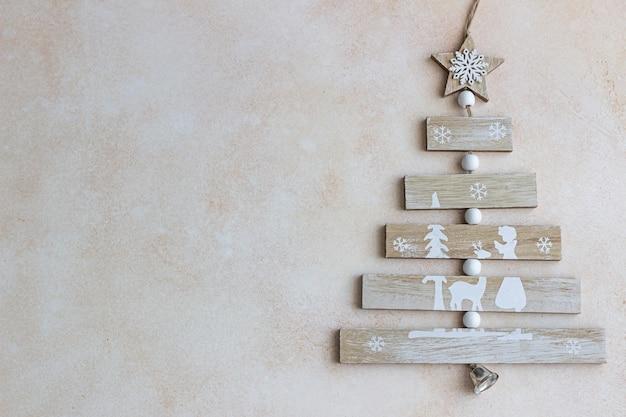 Houten kerstboom op licht beton.