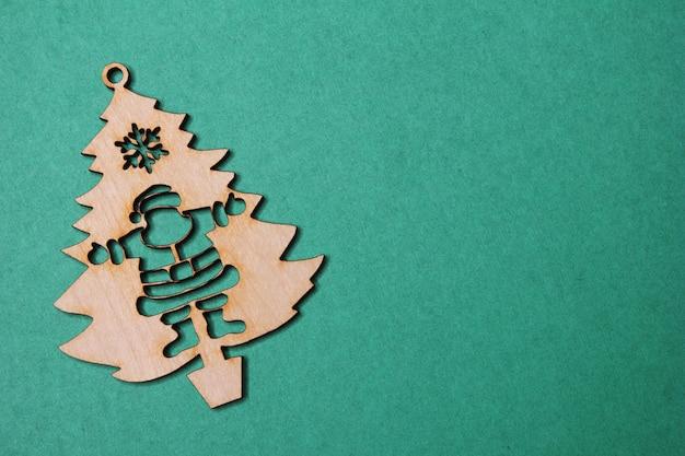 Houten kerstboombeeldje met santa claus op een groene achtergrond.