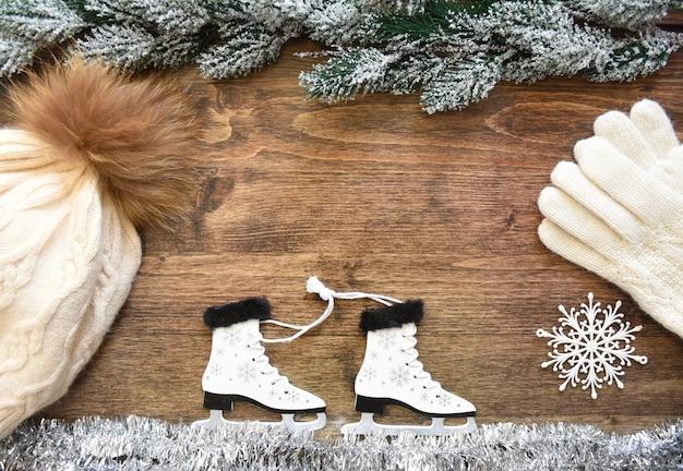 Houten kerstboomspeelgoed schaatsen met sneeuwvlokken vastgebonden met touw op wit klatergoud dat ijs imiteert
