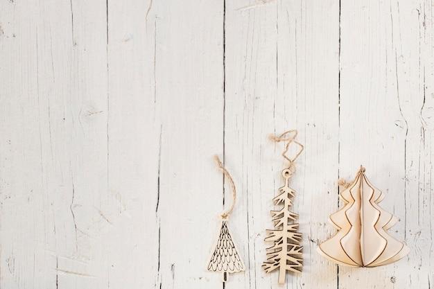 Houten kerstboomversieringen met kopie ruimte op een witte houten achtergrond