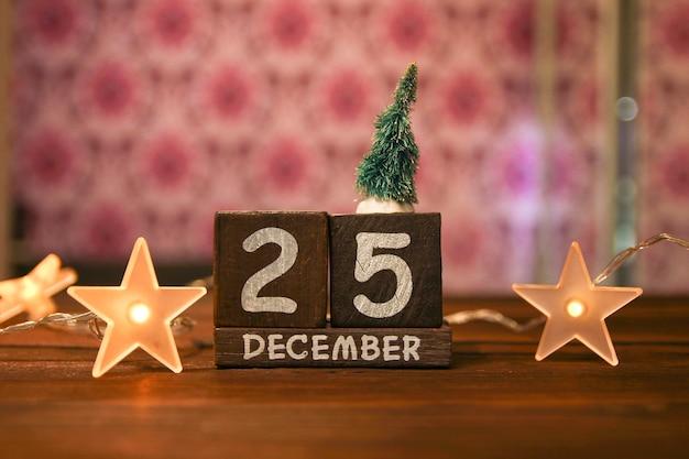 Houten kerstdatum met december als achtergrond