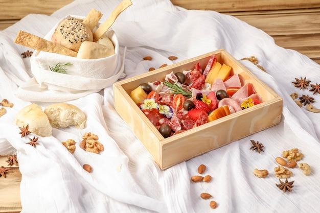 Houten kerstgeschenkdoos, met traditionele italiaanse gebruiksvoorwerpen: rauwe prosciutto, salami, parmezaanse kaas, olijven en brood.