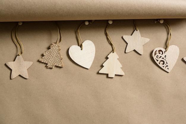 Houten kerstmisspeelgoed op een achtergrond van kraftpapier met exemplaarruimte.