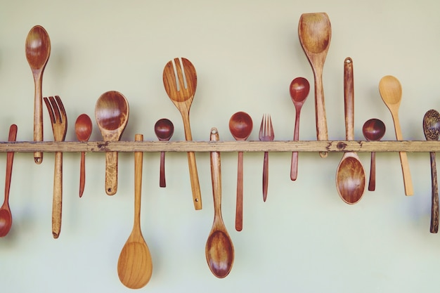 Houten keukengereedschap: houten lepel, houten vork, houten spatel, hangen op witte muur.