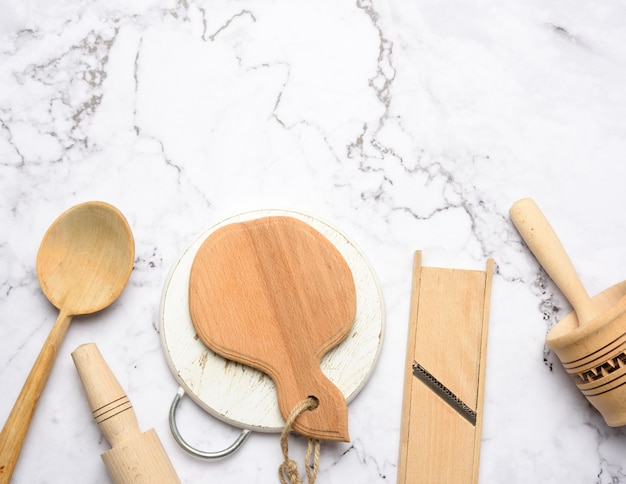 Houten keukengerei op witte marmeren tafel, bovenaanzicht, kopie ruimte