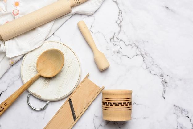 Houten keukengerei op witte marmeren tafel, bovenaanzicht Premium Foto