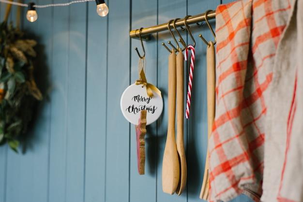 Houten keukenlepel en speelgoed met vrolijke kerst inscriptie, rood grijze handdoek op haken in scandinavische stijl keuken