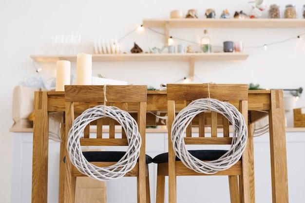 Houten keukenstoelen versierd met kerstkransen in de scandinavische keuken