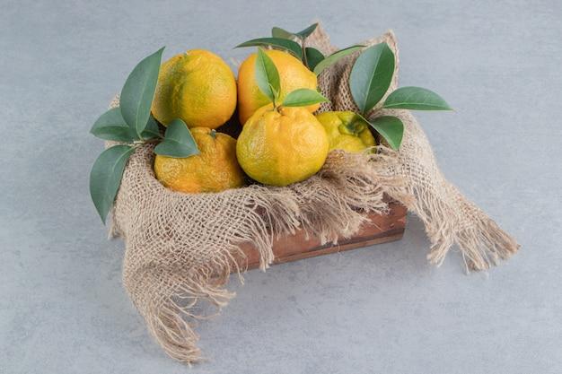 Houten kist bedekt met een stuk stof, gevuld met mandarijnen op marmer.