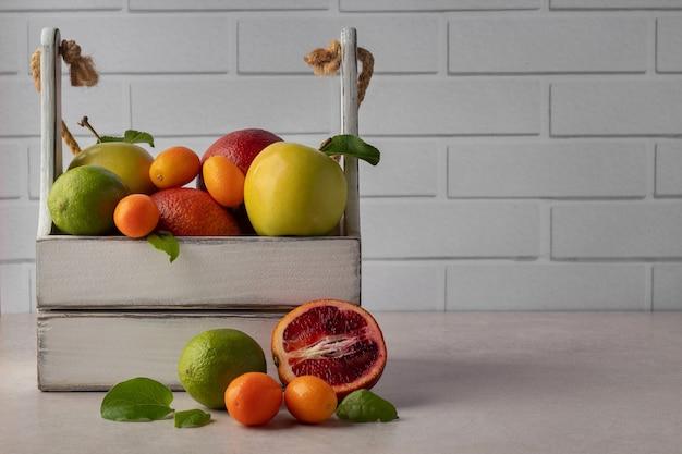 Houten kist met assortiment van tropisch fruit op grijze tafel, kopie ruimte